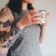 Mujer joven con tatuaje y café