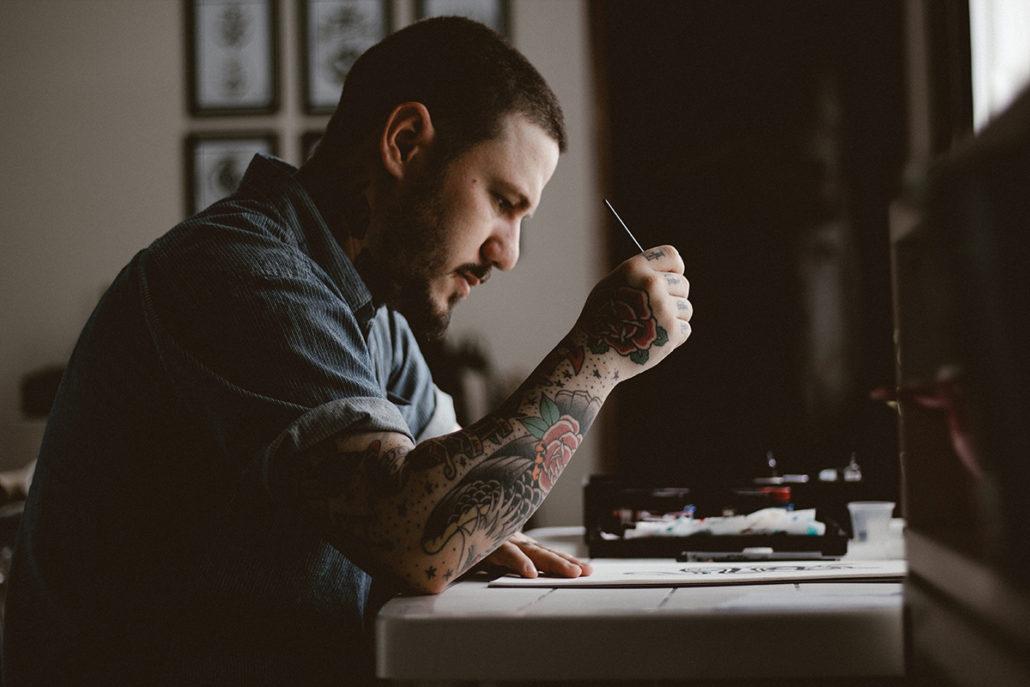 Hombre con tatuajes haciendo el diseño de un nuevo tato